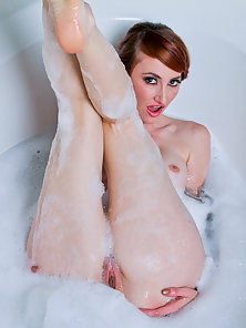 Sizzling redhead takes a masturbation break to test her glass dildo in the bathtub