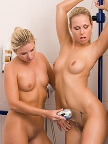 Two pretty young blondes lick pussy and fuck with dildos in the shower