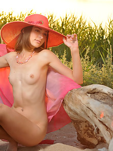 Pretty Teen Chick Sitting on A Sea Beach at the Sun Set Time