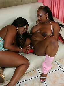 Two Sensual Ebony Sluts Fucking Their Cunts by Sharing a Double Ended Red Dildo