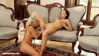 Exotic ladies kissing each others naked bodies in living room